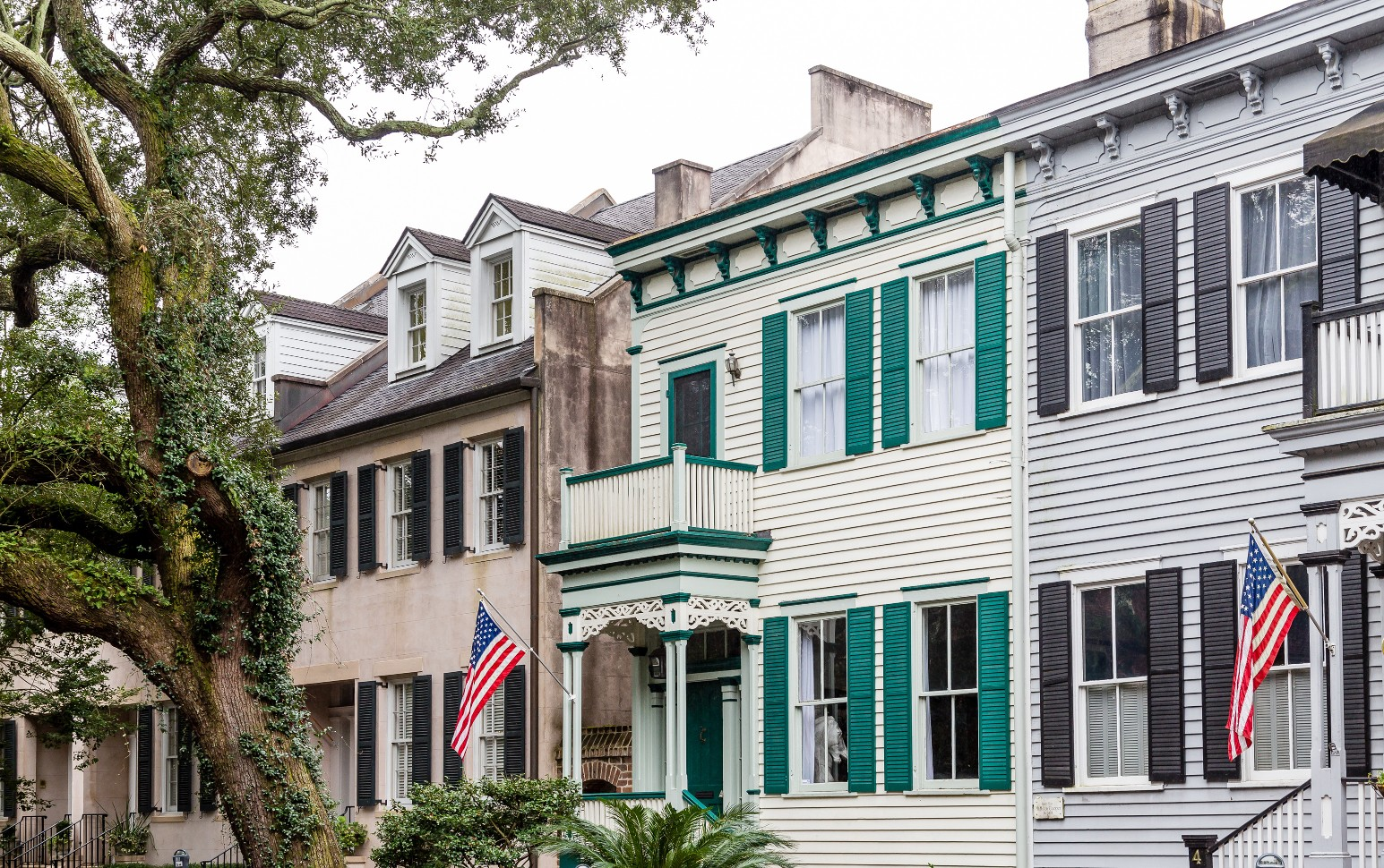 historic charleston home with green shutters and American flag